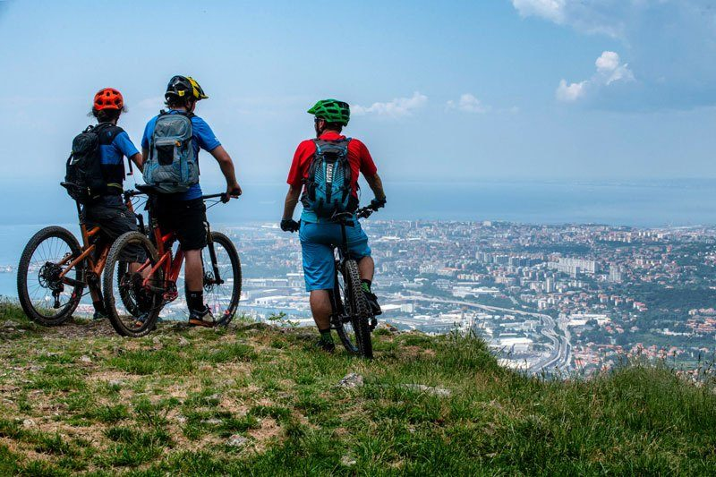 Trans Slovenia 1 bikers with view of Trieste