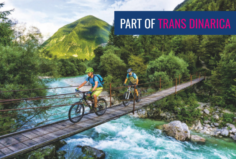 two men biking over soča river bridge part of trans slovenia