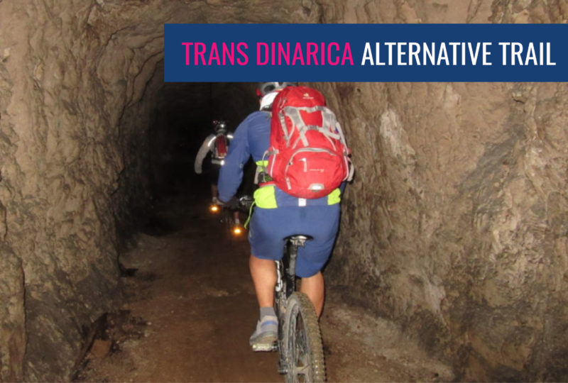 people biking trans slovenia tour through a dark cave