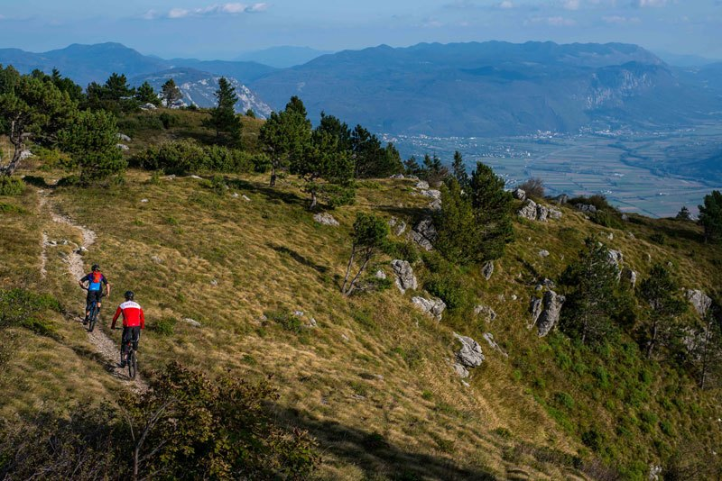 two men biking trans slovenia trail in beautiful nature