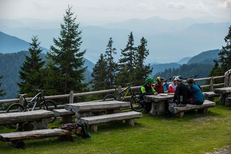 Trans Slovenia 3 bikers at mountain hut with view