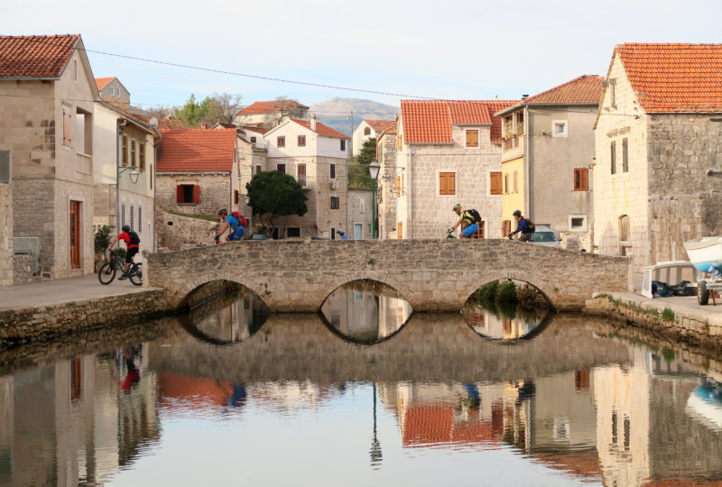Group of people riding bikes through old croatian village with river and bridge