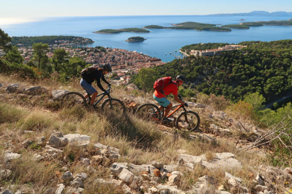Riding with mountain bike with view of croatian islands, sea and town