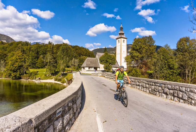 cyclist near bohinj lake with church behind