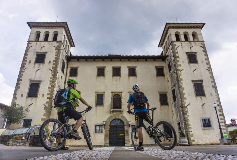 two bikers in front of castle dobrovo